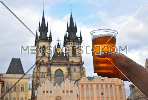 Close up man hand showing disposable plastic glass full of beer over cityscape with Cathedral of Our Lady before Tyn, Prague, Czech Republic