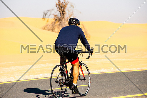cyclist cycling on a track in the desert