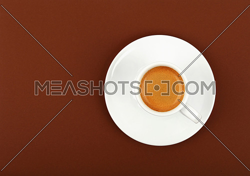 Close up one white cup full of espresso coffee on saucer over brown paper background, elevated top view, directly above