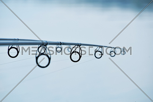 Fishing rod over quiet blue water of lake or river