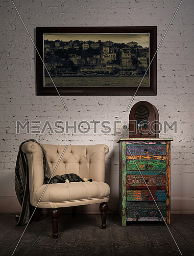 Composition of vintage beige armchair, colorful cupboard, aged wooden radio and hanged painting