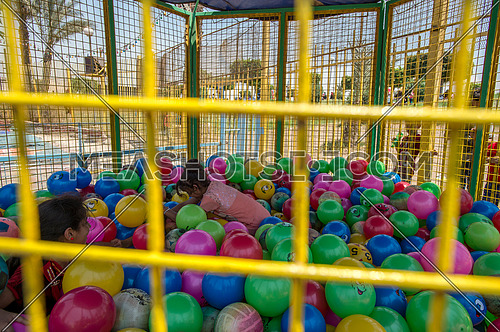 Egyptian kids playing inside a ball den in amusement park during eid al fitr celebration