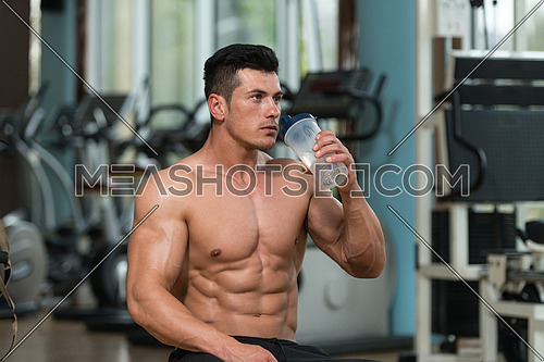 Muscular Man Resting After Exercise And Drinking From Shaker