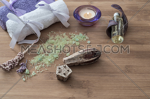 Spa concept. flowers,candles, aromatic salt,soap and bath purple and white towels on wooden background