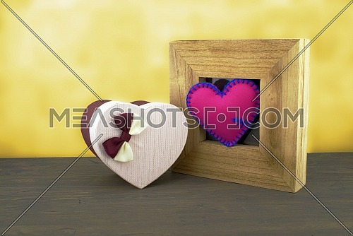 Handcrafted pink heart in a wooden frame with a heart shaped gift box