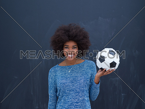 portrait of a beautiful friendly African American woman with a curly afro hairstyle and lovely smile holding a soccer ball isolated on a gray background