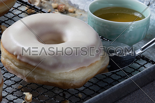 top side view  of white glazed donuts with walnuts aside, hazelnuts and honey