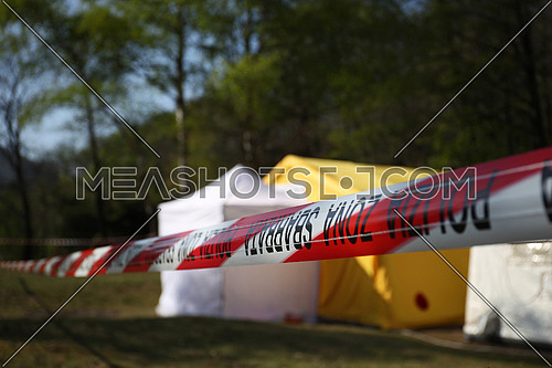 Red and white police line around a crime scene tent in a forest