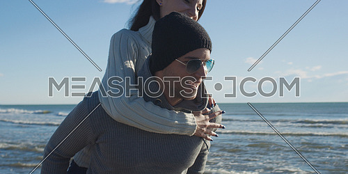 Men Giving Piggy Back Rides At Sunset By The Sea, autumn time