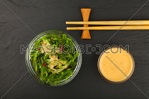Close up bowl of green wakame seaweed salad with satay sauce and chopsticks on black slate board background, elevated top view, directly above