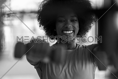 happy healthy african american woman working out in a crossfit gym on weight loss with dumbbells