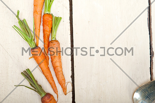 fresh baby carrots over eustic white wood table