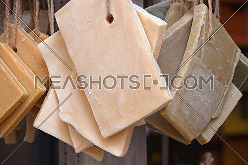 Close up retail display with many souvenir hard soap bars hanging, low angle view