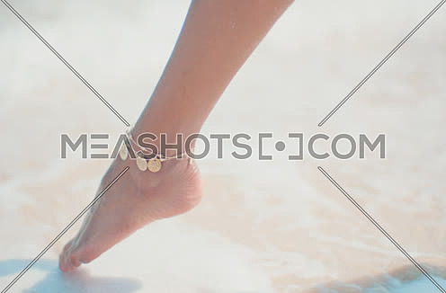 Close up of woman feet on beach.