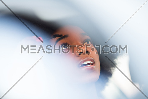 young beautiful African American woman making makeup while driving car