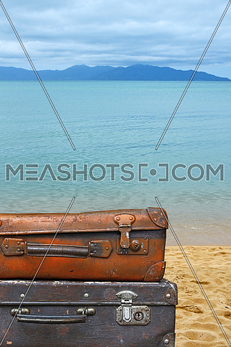 Close up stack of two old vintage antique grunge travel luggage brown leather suitcase trunks isolated over background of sea beach, low angle side view