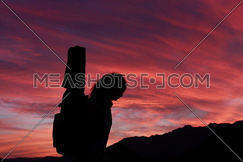 A girl in silhouette carrying her guitar walking by sunset