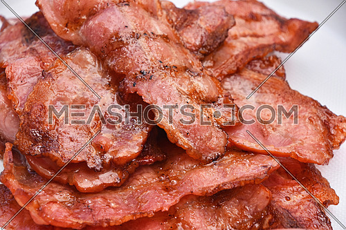 Crispy fried grilled barbecue bacon slices, cooked on bbq smoke grill, close up on white background, full frame crop