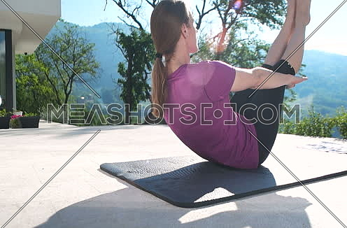 middle age Fitness Woman Doing Stretching on terace in front of villa