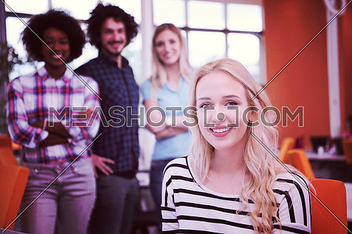 young smiling informal businesswoman working in the office with colleagues in the background