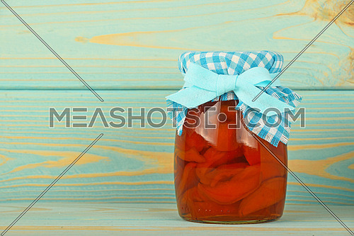 One glass jar of homemade quince jam with textile top decoration at blue painted vintage wooden surface