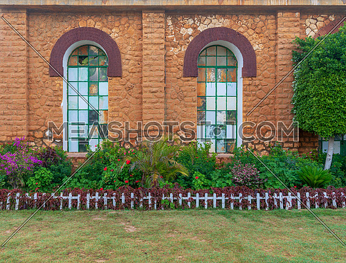 Orange colored bricks stone wall with two big old grunge windows covered with green metal grid, green grass floor, and plants at summer time, Montazah Public park, Alexandria, Egypt