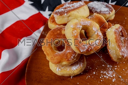 Close up of delicious lush donuts with top over american flag background american independence day, celebration, patriotism and holidays concept