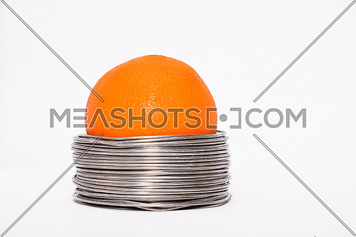 Wired orange: whole orange in coils of aluminium wire isolated on white background