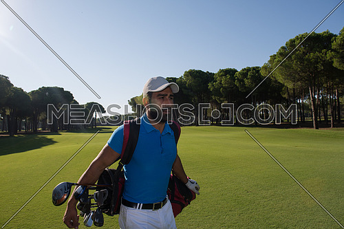 handsome middle eastern golf player carrying and bag  and walking at course on beautiful morning sunrise