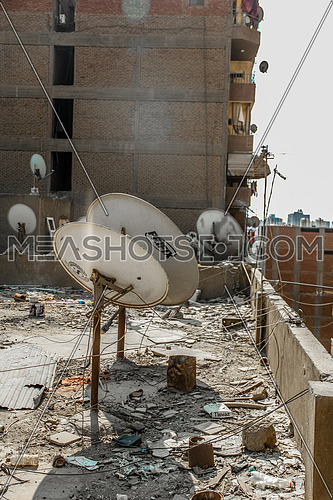 Long shot for messy Roof of Egyptian House with a lot of satellite dishes at day