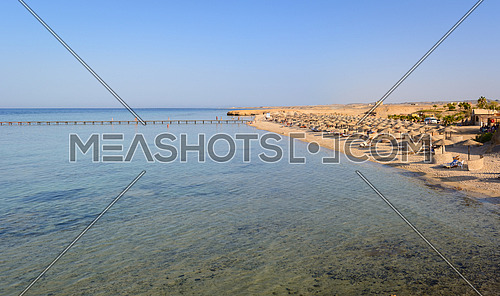 Egyptian beaches with typical parasols in the background and red sea in frontground
