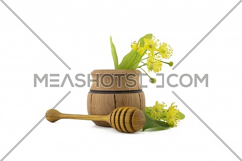 Small wooden pot of freshly picked yellow linden flowers and leaves, also called tilia and wooden wand over a white background