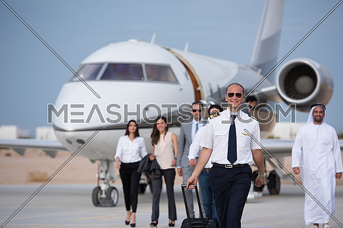 Young middle eastern successful pilot walking with clients in front of private airplane