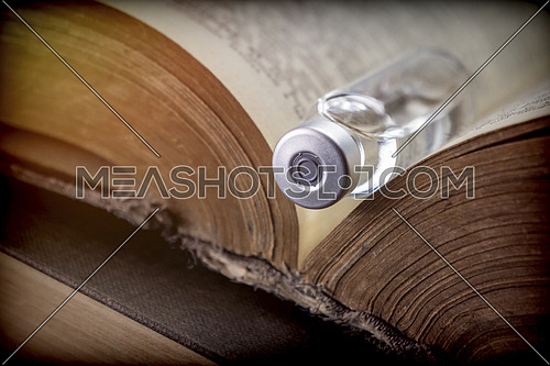 Vial on an old book of medicine, conceptual image