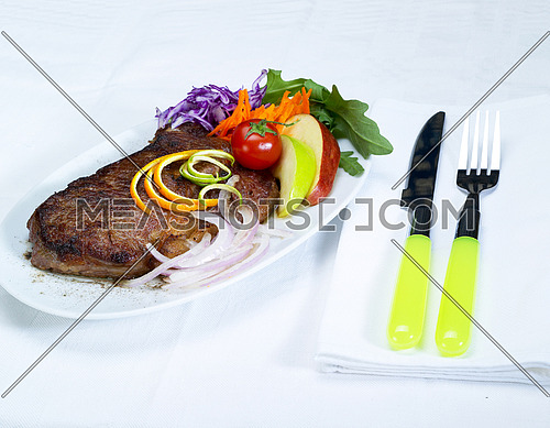 fresh juicy beef ribeye steak grilled with lemon and orange peel on top and vegetables beside
