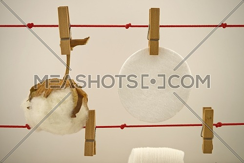 Round cotton pads and natural cotton boll hanging on laundry clips. Concept of reusable washable pads
