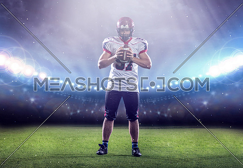 portrait of confident American football player holding ball while standing on the big modern stadium with lights and flares at night
