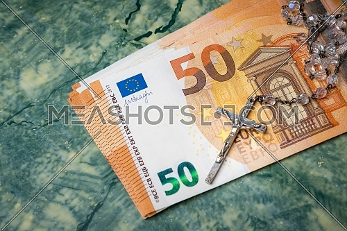 Silver rosary and euro money on green table,concept photo.