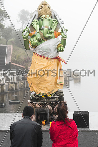 A kneeling man and woman pray in front of a Hindu deity, Grand Bassin Mauritius