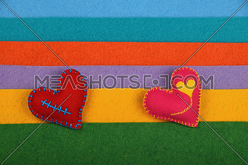 Craft and art, two handmade stitched toy hearts, pink and red on colorful felt stripes background