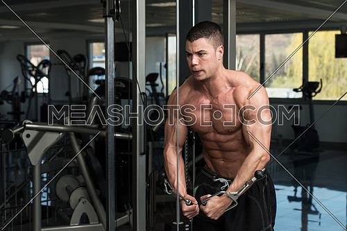 Young Bodybuilder Is Working On His Chest With Cable Crossover In A Dark Gym