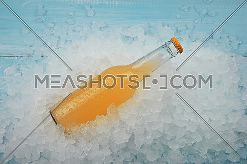 Close up one glass bottle of cold orange cocktail on crushed ice at retail display, high angle view
