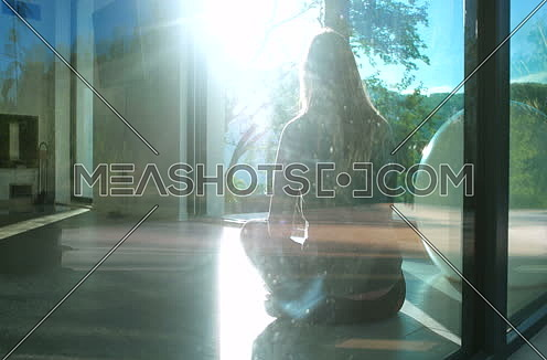 Young Woman Doing Yoga in morning in luxury villa by window