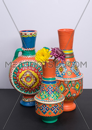 Studio shot of still life of three orange ornate pottery vases with two yellow and violet flower in a background of black table and white wall