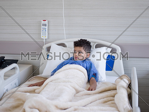 young boy patient lies in a hospital bed