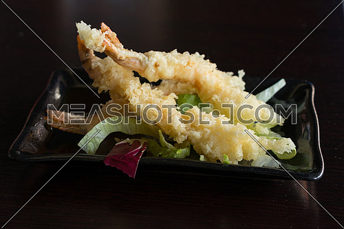 Japanese Cuisine - Tempura Shrimps (Deep Fried Shrimps) with sauce and vegetables on a black plate. Black background,shallow depth of field.
