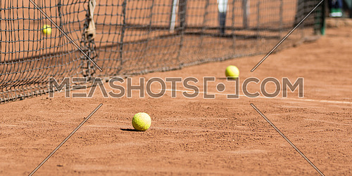 tennis court and two balls beside the net