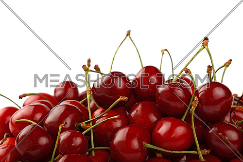 Heap of fresh red ripe sweet black cherry isolated on white, close up, low angle view