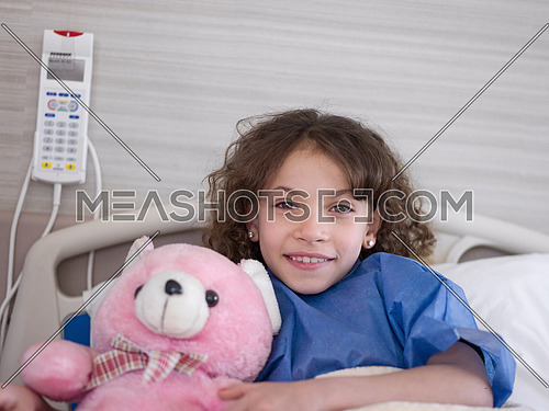 young girl lies in a hospital bed while hugs  pink teddy bear portrait