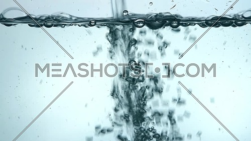 Pouring pure clear cold water in transparent glass jar or teapot until full, close up, low angle side view, slow motion
